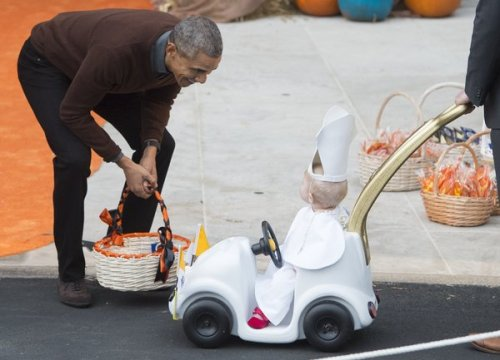"US President Barack Obama greets a young child dressed as the Pope and riding in a ""Popemobile"" as he hands out treats to children trick-or-treating for Halloween on the South Lawn of the White House in Washington, DC, October 30, 2015. AFP PHOTO / SAUL LOEB        (Photo credit should read SAUL LOEB/AFP/Getty Images)"